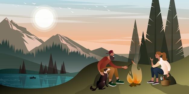 Joven pareja con un perro en un alto cerca de una fogata en las montañas en una cálida noche de verano.