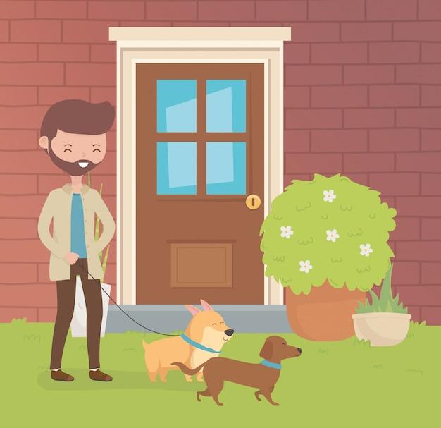 Joven con perros pequeños mascotas en el jardín de la casa
