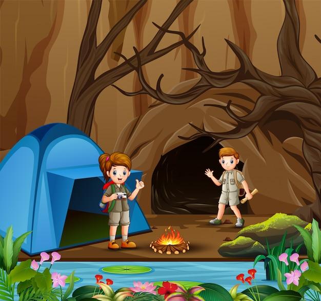 Joven scout niño y niña en la escena de la zona de camping