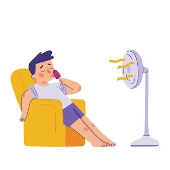 Joven sentado y lamiendo paletas delante del ventilador de pie