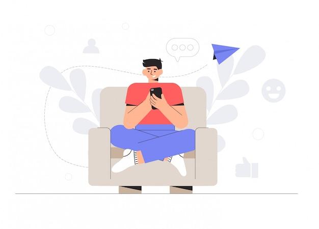 Joven está sentado en la silla y hablando por teléfono en las redes sociales.