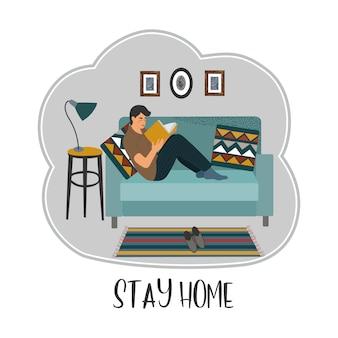 Joven sentado en un sofá y leyendo un libro en un apartamento en cuarentena.