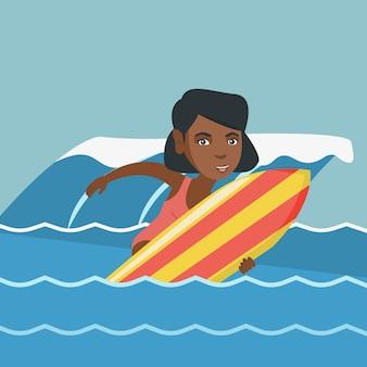 Joven surfista afroamericano en una tabla de surf.