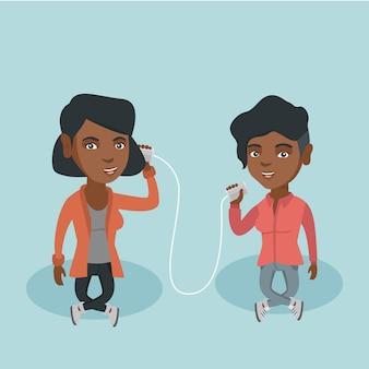 Jóvenes amigos africanos hablando por teléfono de lata.