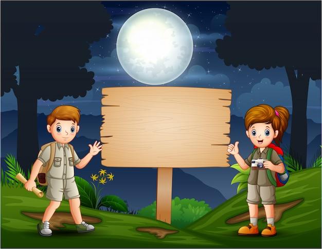 Jóvenes exploradores caminando en el bosque por la noche
