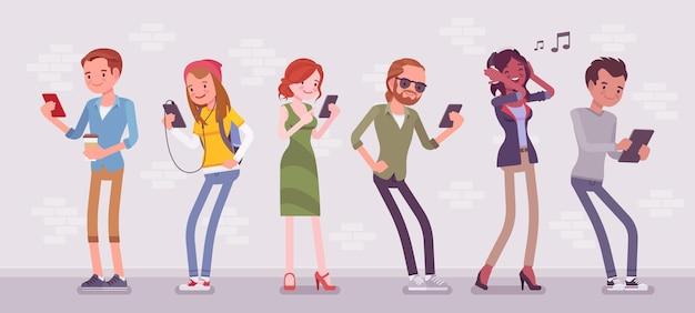 Jóvenes con gadgets de pie usando un teléfono inteligente para llamar, jugar, ver películas, escuchar música, comunicarse con amigos a través de mensajes de texto, chats de video