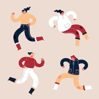Jóvenes con ropa de invierno saltando sobre fondo rosa