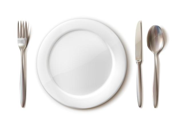 Juego de cubiertos de plato blanco, tenedor, cuchara y cuchillo aislado en blanco