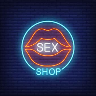 Labios con letras de sex shop en círculo. letrero de neón en el fondo de ladrillo.
