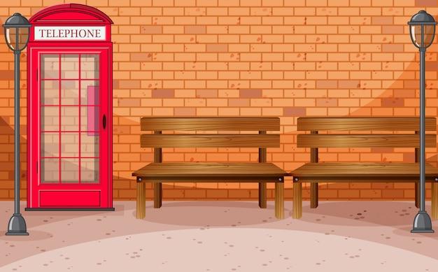 Lado de la calle de pared de ladrillo con cabina telefónica y banco