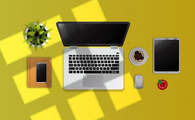 Laptop, gadget, notebook, una taza de café vista superior en el escritorio amarillo con luz solar de la ventana