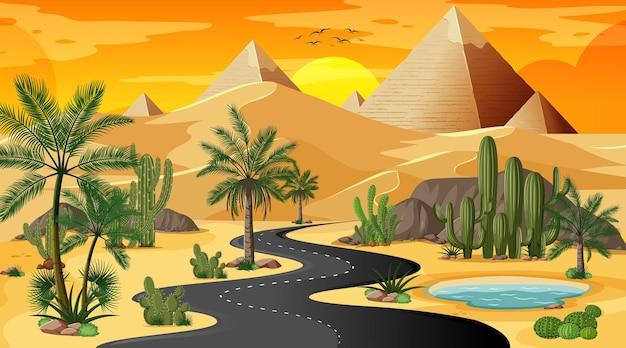 Largo camino a través del paisaje forestal del desierto en la escena del atardecer con la pirámide de giza.