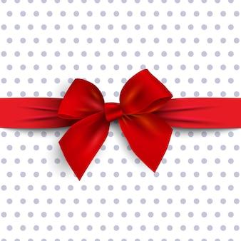 Lazo de regalo rojo con cinta sobre fondo de lunares