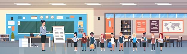 Lección escolar maestra con alumnos parados frente a la mesa en el aula
