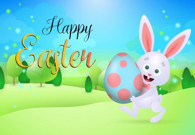 Letras felices de pascua con el conejito que lleva el huevo en prado