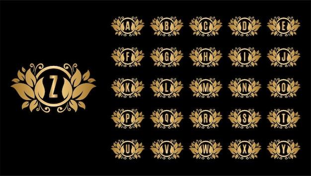 Letras mayúsculas de fuente de alfabeto dorado con hojas y salpicaduras de oro.