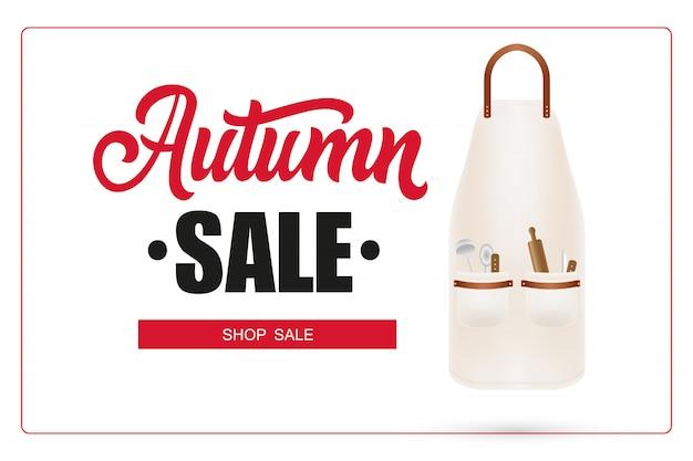 Letras de venta de otoño en marco y delantal con utensilios de cocina