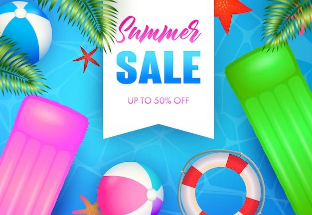 Letras de venta de verano, balsa flotante, pelotas de playa y salvavidas.
