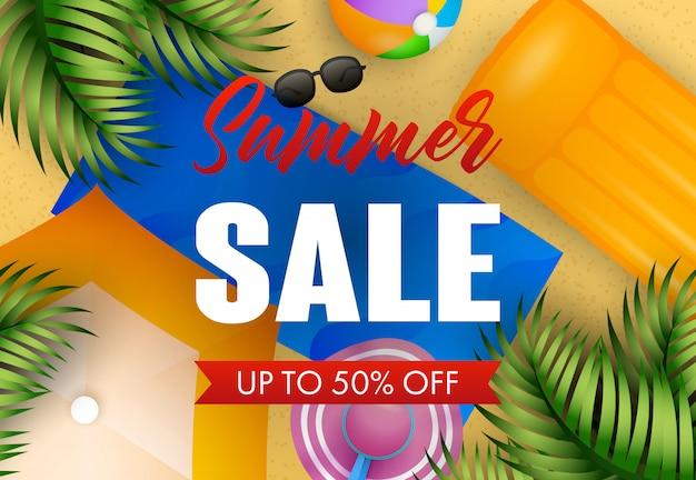 Letras de venta de verano con tapete de playa, gorro, pelota y colchón de aire.