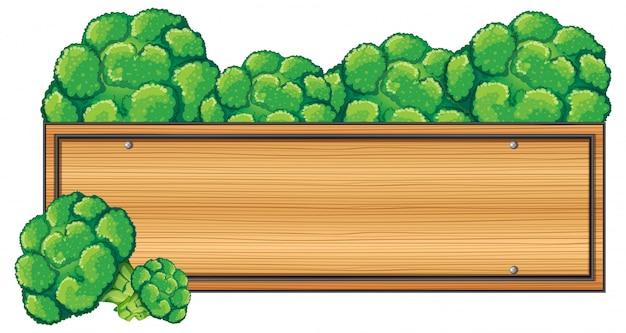 Letrero de madera con brócoli en la parte superior.