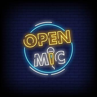 Letrero de neón de micrófono abierto en pared de ladrillo