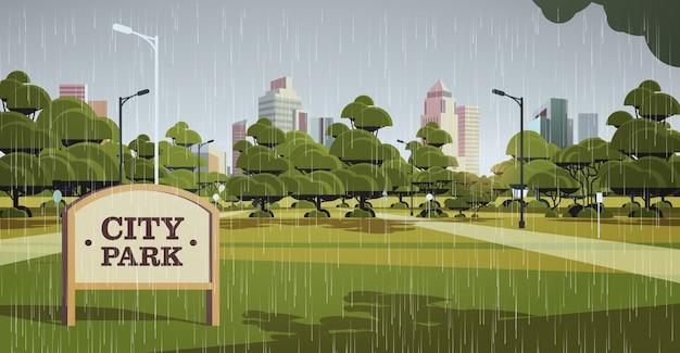 Letrero en el parque de la ciudad gotas de lluvia cayendo lluvioso día de verano horizonte skyskraper edificios paisaje urbano