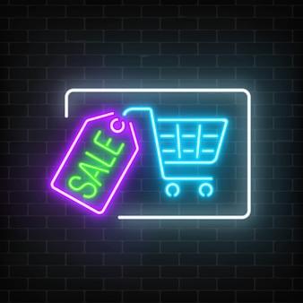 Letrero de venta brillante de neón con carrito de compras y etiqueta en una pared de ladrillo oscuro letrero publicitario luminoso.