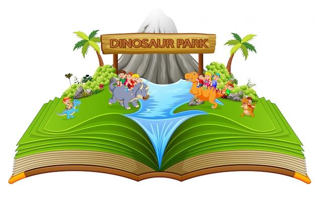 El libro de cuentos verde del parque de dinosaurios con los niños en él.