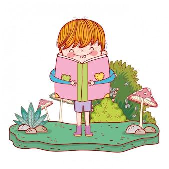 Libro de lectura feliz del niño pequeño en el paisaje