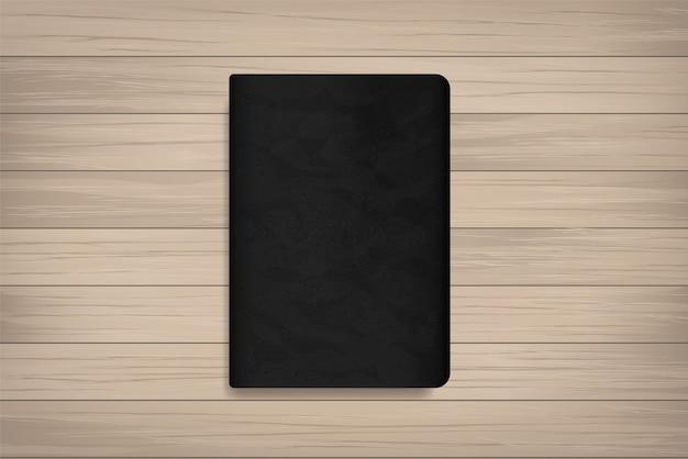 Libro con tapa negra sobre madera.