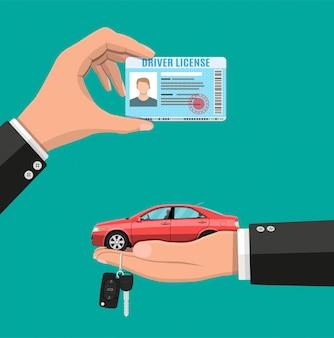 Licencia de conducir en mano y auto sedán con llaves