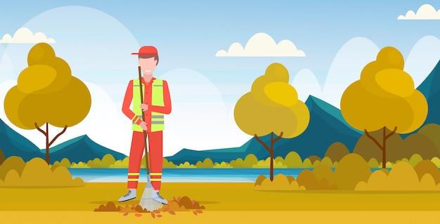 Limpiador de calles masculino con rastrillo hombre barrer rastrillo de césped deja servicio de limpieza concepto parque de la ciudad paisaje de fondo plano horizontal