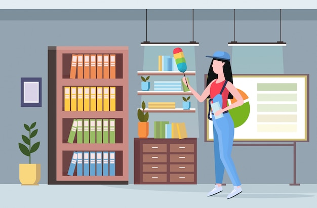 Limpiador de mujer en uniforme con cepillo de polvo conserje femenino para desempolvar estanterías concepto de servicio de limpieza profesional centro de trabajo creativo moderno interior de la oficina horizontal de longitud completa plana