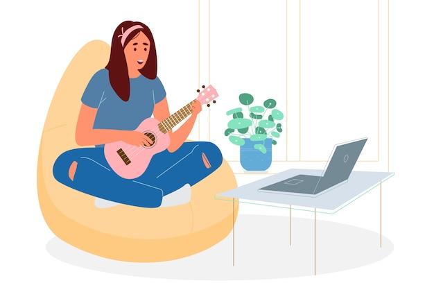 Linda adolescente sentada en una silla puf con rezagos cruzados aprendiendo a tocar el ukelele en línea.