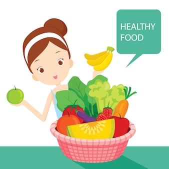 Linda chica con alimentos limpios, frutas y verduras en la canasta, comida sana