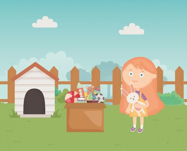Linda chica con caja de juguetes y casa de perro en el patio trasero