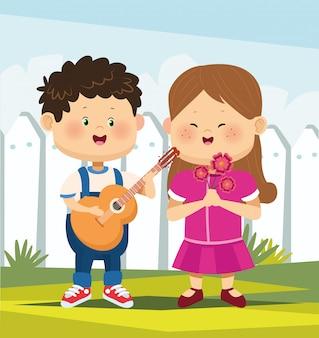 Linda chica enamorada y niño tocando la guitarra sobre valla blanca