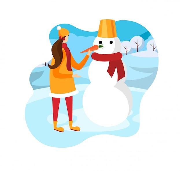 Linda chica feliz jugando con muñeco de nieve vestido divertido