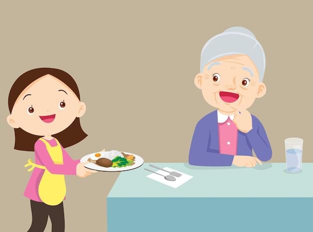 Linda chica sirviendo comida a la abuela mayor anciana