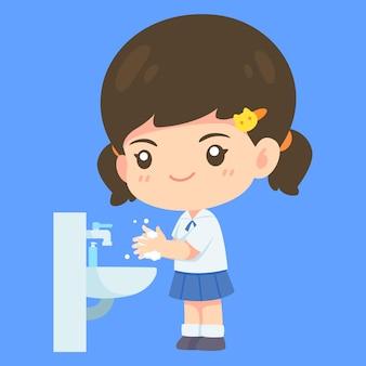 Linda chica en uniforme de estudiante lavándose las manos