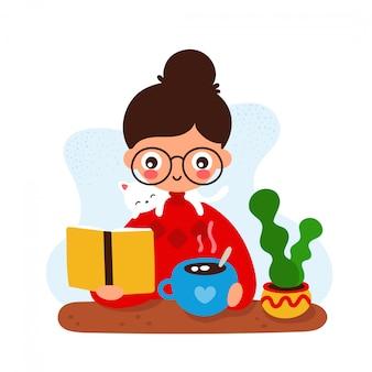 Linda joven sonriente feliz en un escritorio con un libro, una taza y un gato.