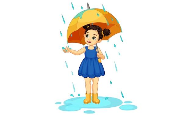 Linda niña con paraguas disfrutando de la lluvia