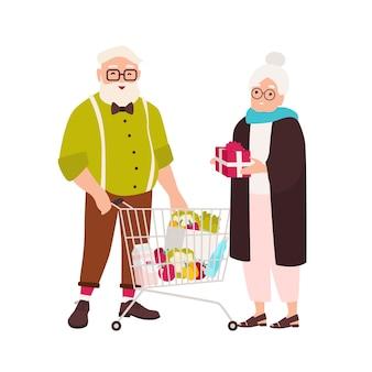 Linda pareja de ancianos con carrito de compras lleno de productos alimenticios y caja de regalo