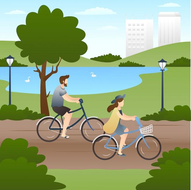 Linda pareja andar en bicicleta en el parque.