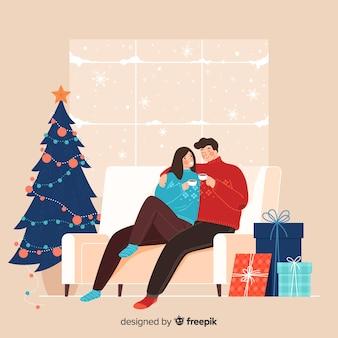 Linda pareja disfrutando de su café junto a un árbol de navidad