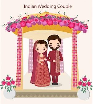 Linda pareja india en traje de novia tradicional de pie bajo el mandap de boda