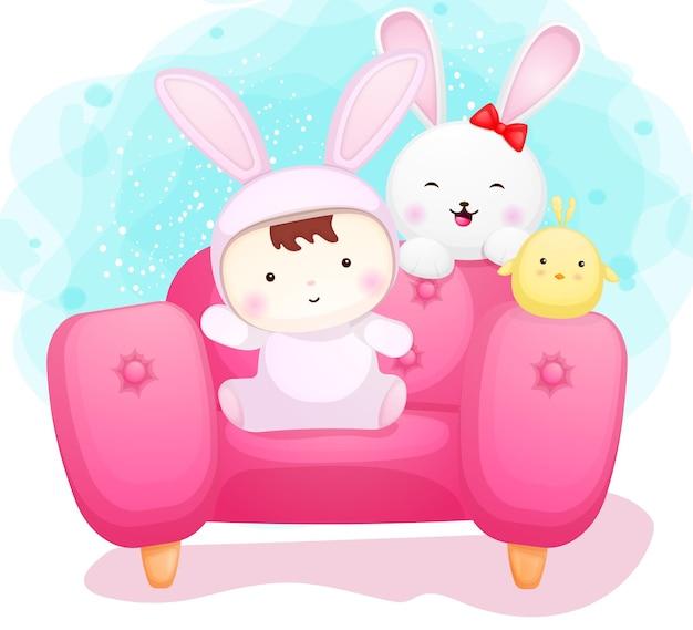 Lindo bebé disfrazado de conejito y amigos en el sofá