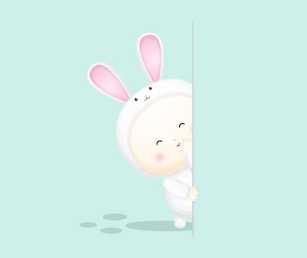 Lindo bebé disfrazado de conejito detrás de una pared. ilustración de dibujos animados vector premium