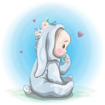 Lindo bebé sentado en un traje de conejo.