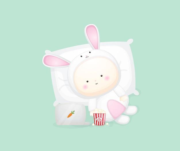 Lindo bebé en traje de conejito acostado y viendo la película. ilustración de dibujos animados vector premium